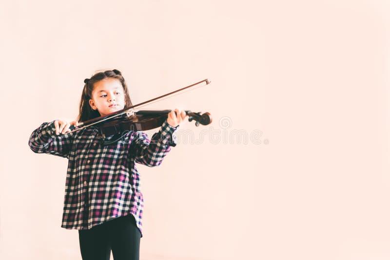 Weibliches Kind der Mischrasse, das Violinen-, Kindererziehungs- oder Musikkonzept, mit Kopienraum spielt stockbilder