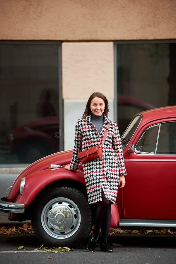 Download Weibliches Lehnen Des Brunette Auf Dem Roten Retro- Auto, Kamera Betrachtend Stockfoto - Bild von mädchen, lebensstil: 106803158