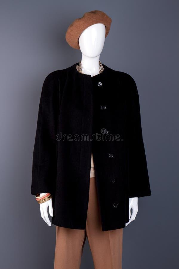Weibliches Mannequin gekleidet im schwarzen Mantel lizenzfreie stockbilder