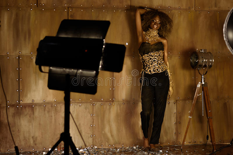 Weibliches Modell des eleganten Afroamerikaners im Goldzubehör, das nahe Studiolicht steht und aufwirft, blitzt stockbild