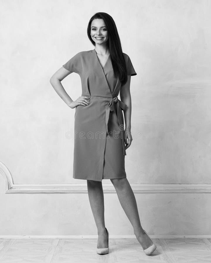 Weibliches Modell in purpurrotem Bauerntrickmidi-Kleid stockfotos