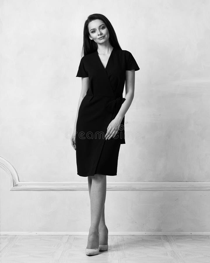 Weibliches Modell in schwarzem Bauerntrickmidi-Kleid stockfoto