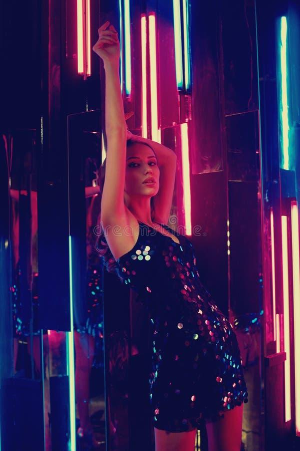 Weibliches Modell in schwarzem glänzendem cami Kleid, das auf großem Würfel sitzt und lizenzfreie stockfotos