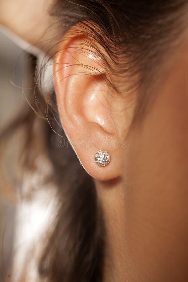 Weibliches Ohr mit Ohrring stockbild