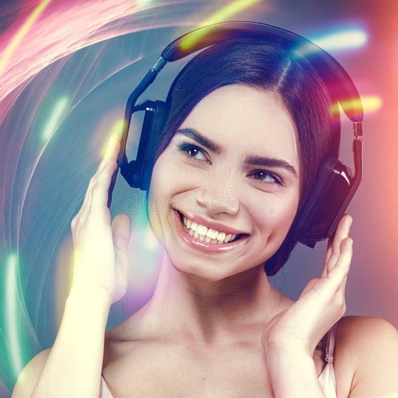 Weibliches Porträt der Schönheit mit Kopfhörern stockfotos
