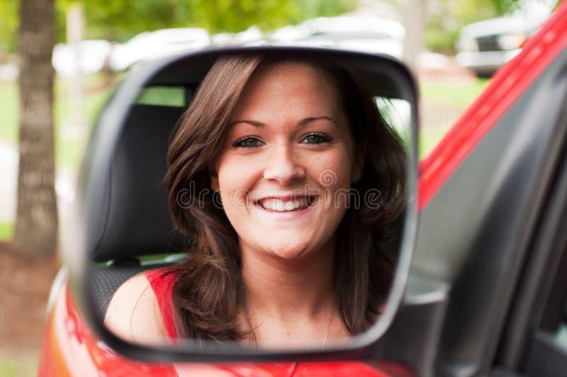 Weibliches Portrait im Fahrzeug-Spiegel lizenzfreies stockfoto