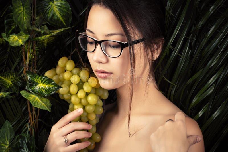 Weibliches recht koreanisches Mädchen in den Gläsern mit Trauben stockfoto