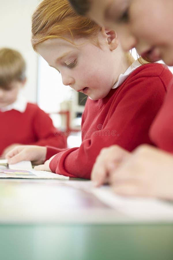 Weibliches Schüler-Lesebuch bei Tisch stockfoto