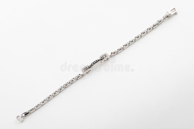 Weibliches silbernes glänzendes Armband mit den Schwarzweiss-Steinen lokalisiert auf weißem Hintergrund lizenzfreie stockfotos