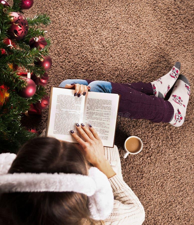 Weibliches Sitzen auf Bodenteppich und Lesebuch nahe bei Weihnachtsbaum und Kaffeetasse stockbilder