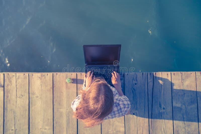Weibliches Sitzen auf hölzernem Dock und Funktion auf Laptop stockbilder