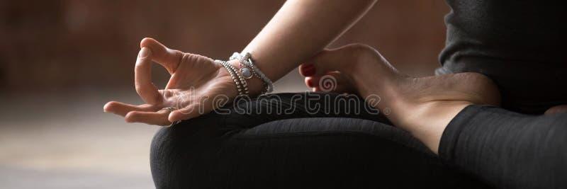 Weibliches Sitzen der horizontalen Bildnahaufnahme in übendem Yoga des Lotussitzes stockbilder