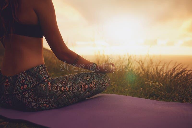 Weibliches Sitzen in der Lotosyogahaltung auf Übungsmatte stockfoto