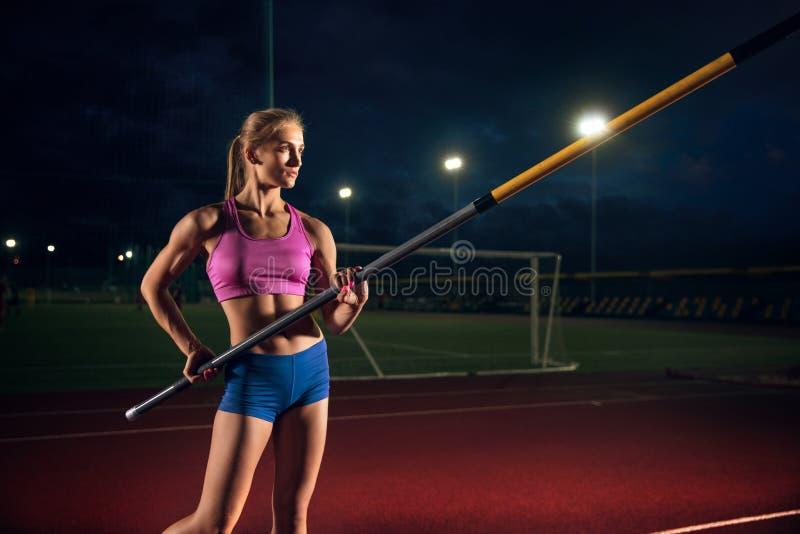 Weibliches Stabhochspringertraining am Stadion am Abend lizenzfreies stockfoto