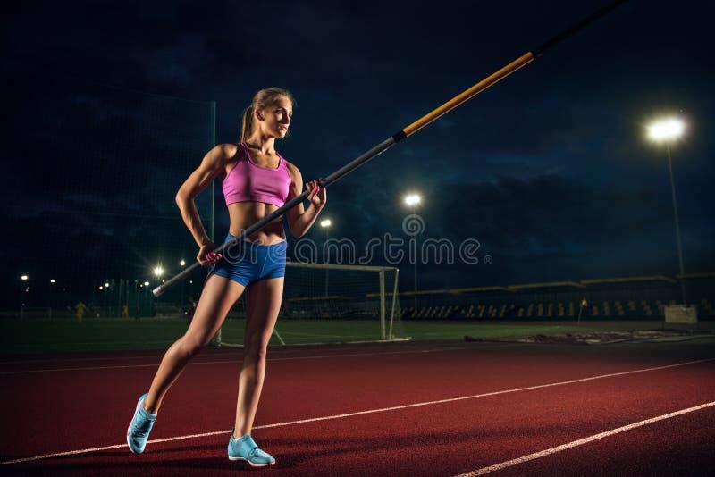 Weibliches Stabhochspringertraining am Stadion am Abend stockfotos