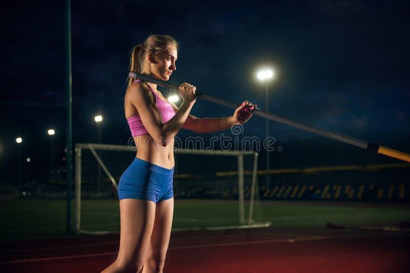 Weibliches Stabhochspringertraining am Stadion am Abend lizenzfreie stockfotos