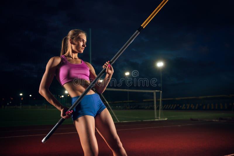 Weibliches Stabhochspringertraining am Stadion am Abend stockbild