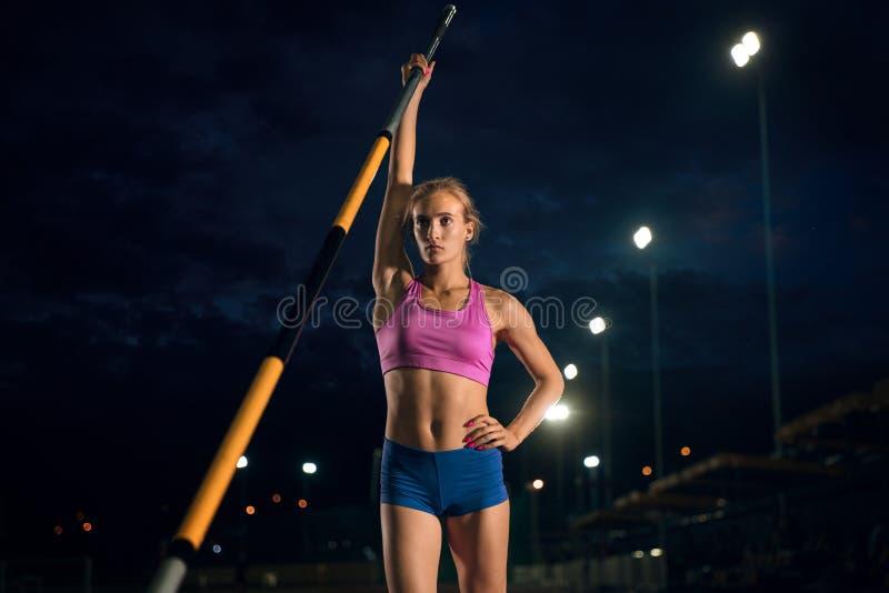 Weibliches Stabhochspringertraining am Stadion am Abend lizenzfreie stockbilder