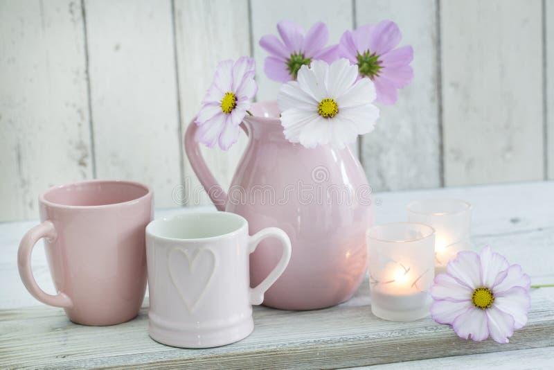 Weibliches Stillleben mit Kerzen, einem Herzbecher und Blumen stockfotos