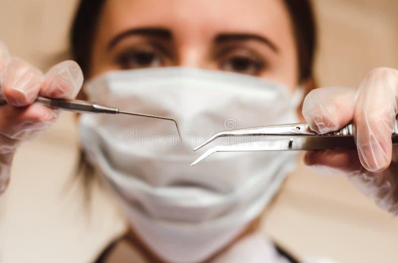 Weibliches stomatologist hält medizinische Instrumente schließen oben lizenzfreies stockfoto