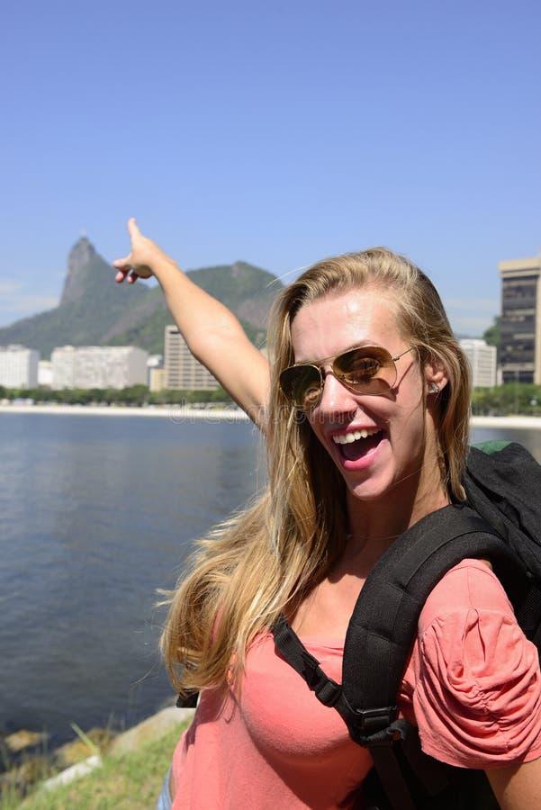 Weibliches touristisches Reisen bei Rio de Janeiro, der auf den Christus-Erlöser zeigt. stockfotografie