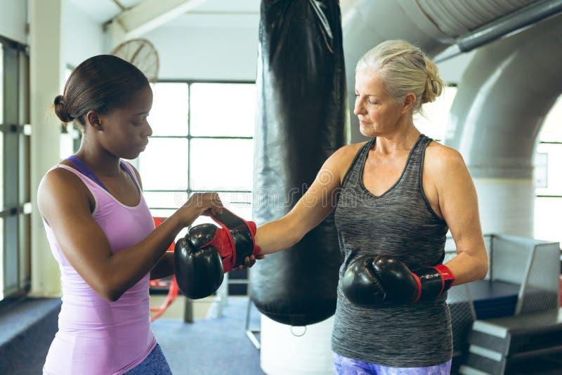 Weibliches Trainerhelfen athletisch Handschuhe in Sportzentrum überziehen lizenzfreies stockfoto
