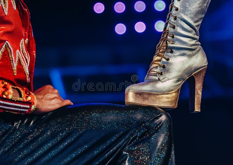 Weibliches und männliches Bein der Füße der Kabaretttänzer-Frauen in den hochhackigen Stiefelkarnevals-Tänzerbeinen auf Tanzboden stockfotografie
