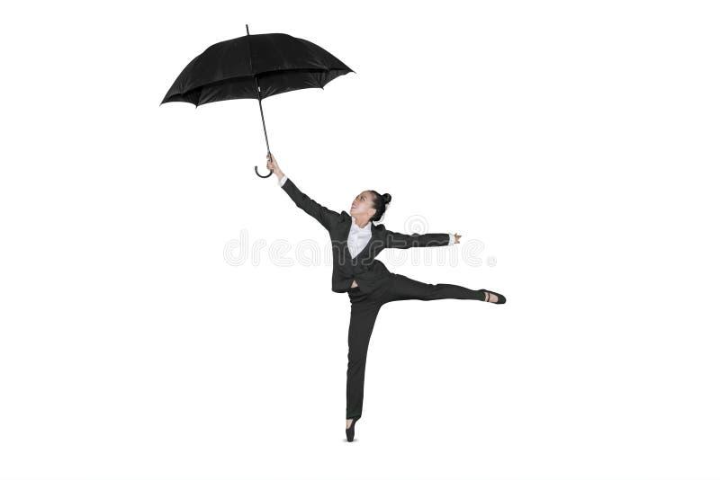Weibliches Unternehmertanzen mit Regenschirm auf Studio stockfotos
