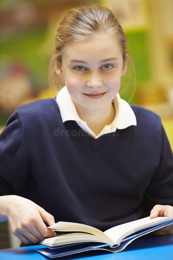 Weibliches Volksschule-Schüler-Lesebuch im Klassenzimmer stockbild