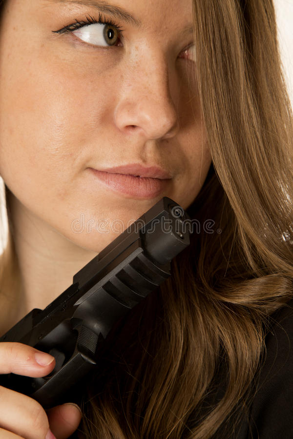 Weibliches vorbildliches Flüchtig blicken des Brunette eine schwarze Pistole seitlich, halten lizenzfreies stockbild