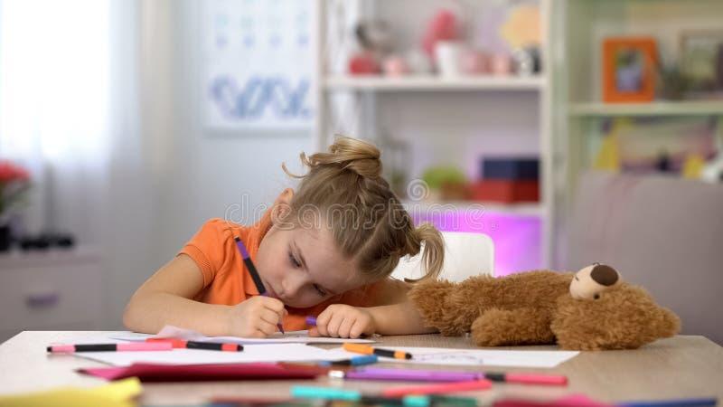 Weibliches Vorschülerzeichnungsbild, Teddybär, der auf Tabelle, glückliche Kindheit, Hobby liegt lizenzfreies stockbild