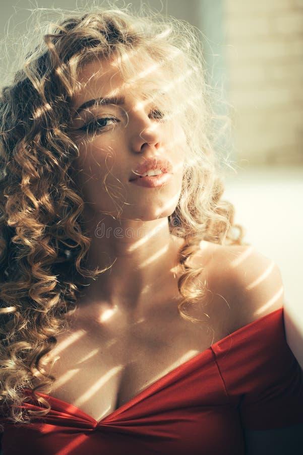 Weibliches Zaubergesicht mit langer blonder Frisur Schönheit mit dem gelockten Haar und perfektem Make-up stockfotografie