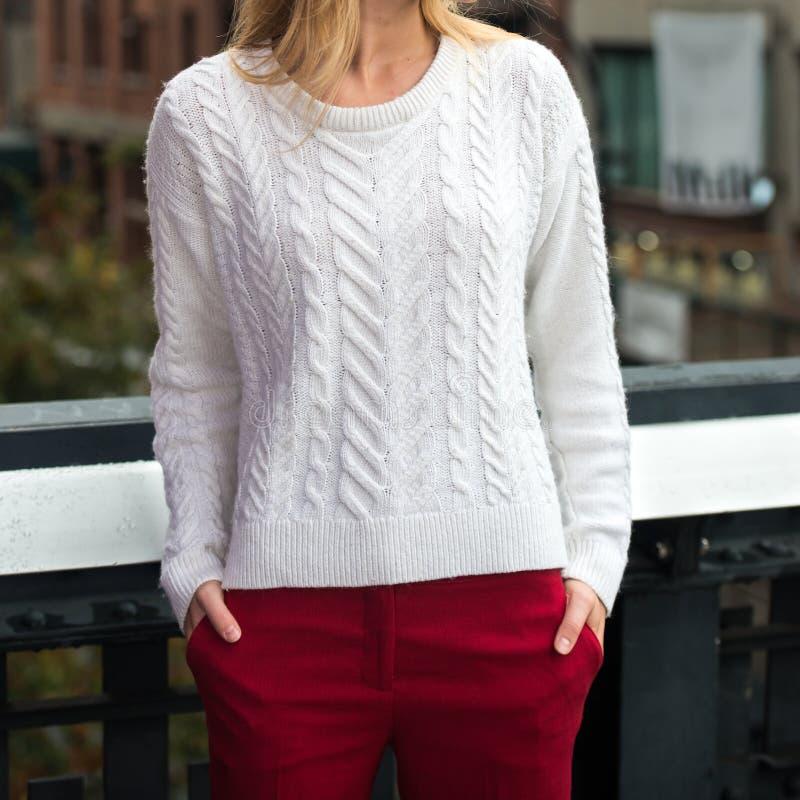Weibliches zufälliges Frühlingsherbst-Ausstattungsweiß strickte Strickjacke und rote Baumwollhose draußen stockbilder