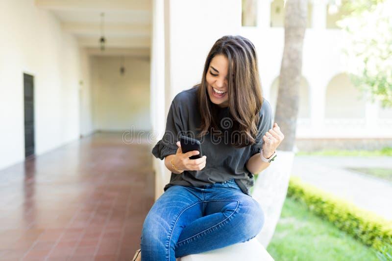 Weibliches Zujubeln beim Aufpassen des Sports am Handy am Campus stockfotos