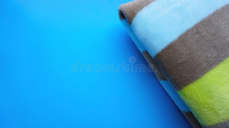 Weiche blaue Decke auf blauem Hintergrund Herbstkomfort, Raum für Text, Draufsicht lizenzfreie stockfotografie