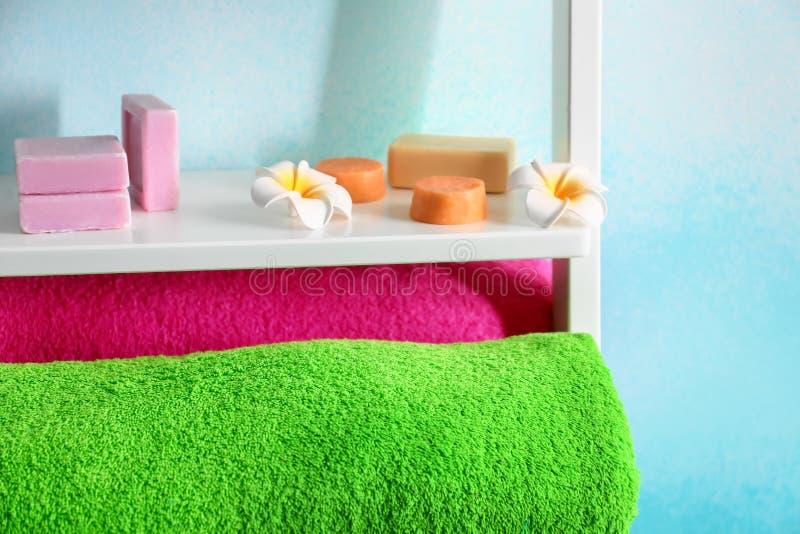 Weiche Farbtücher, -blumen und -seife auf Regal nahe heller Wand, Nahaufnahme lizenzfreie stockfotografie
