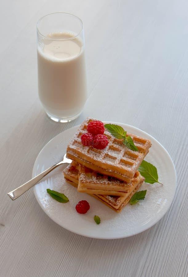 Weiche Waffeln mit Himbeeren und einem Glas Milch, auf einem weißen Hintergrund lizenzfreie stockbilder