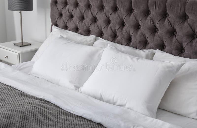 Weiche weiße Kissen auf bequemem Bett stockfoto
