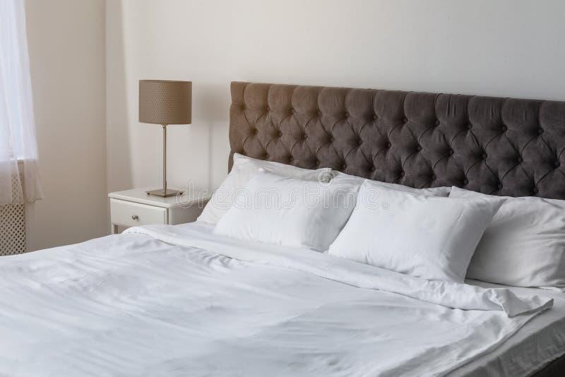 Weiche weiße Kissen auf bequemem Bett lizenzfreie stockfotos