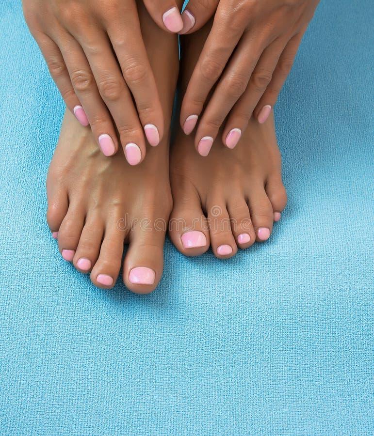 Weiche weibliche Füße und Hände mit Pediküre und Maniküre lizenzfreie stockfotografie