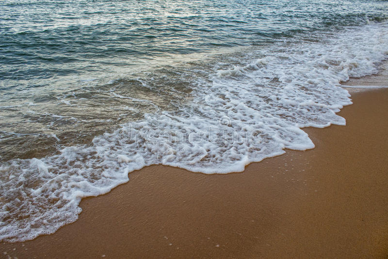 Weiche Welle auf dem sandigen Strand stockbilder