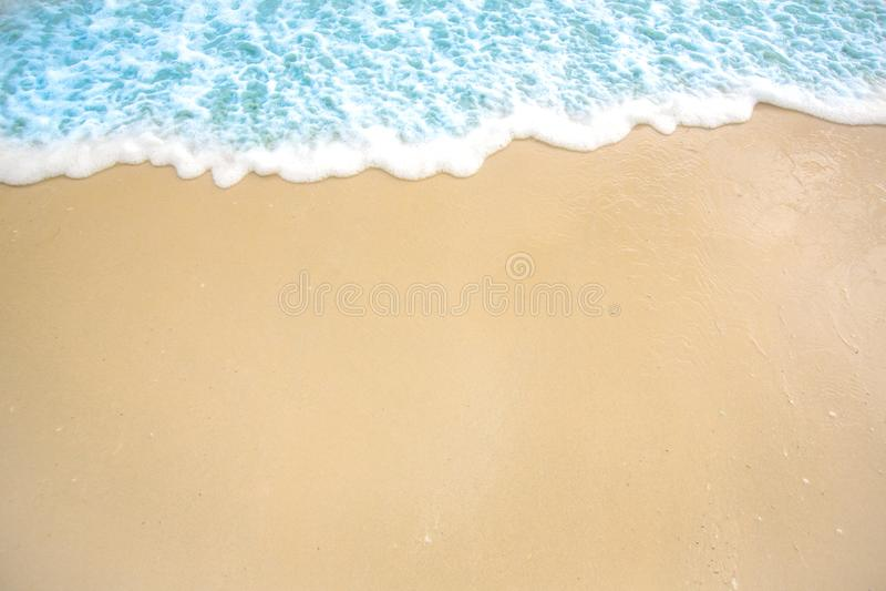 Weiche Welle von blauem Ozean auf sandigem Strand Hintergrund Selektiver Fokus weißer Schaum des Strandes und des tropischen Meer stockfotografie