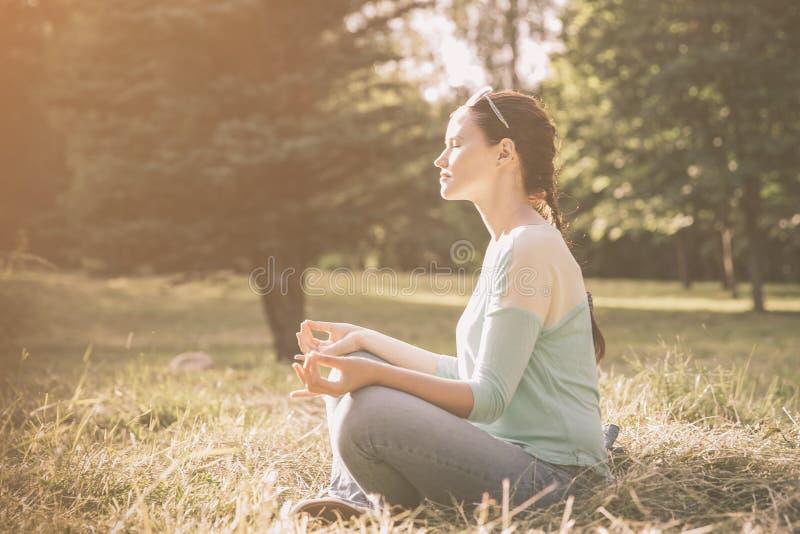 Weicher Fokus Junge Frau, die draußen in Lotussitz meditiert lizenzfreie stockfotos