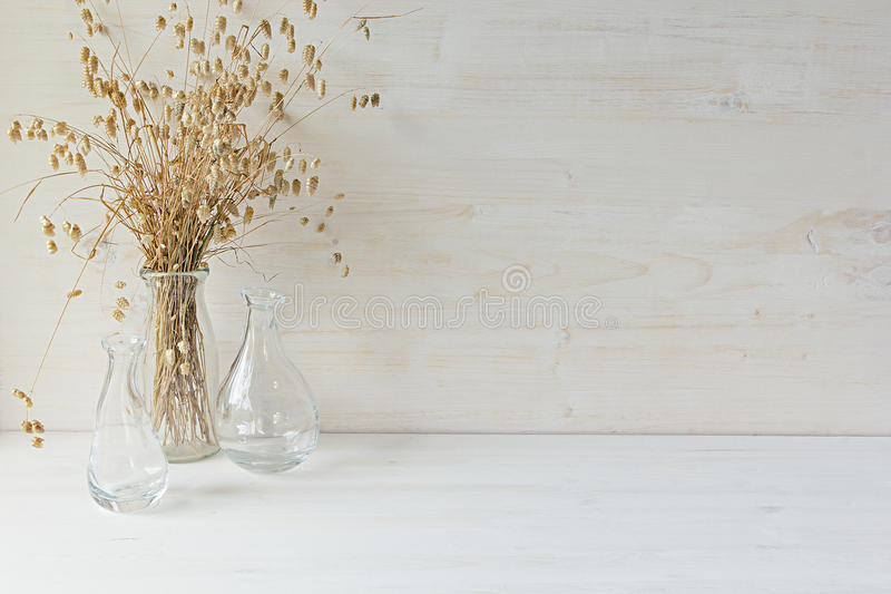 Weicher Hauptdekor des Glasvase mit den Ährchen auf weißem hölzernem Hintergrund stockfotografie