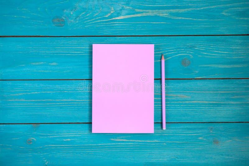 Weicher rosa Notizblock und Bleistift auf hölzernem Hintergrund des Türkises fla stockbild