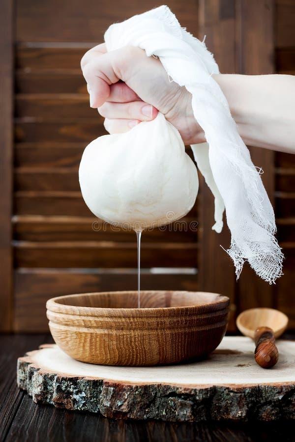 Weicher selbst gemachter frischer RicottaHüttenkäse gemacht von der Milch, laufend auf Musselinstoff aus stockbild