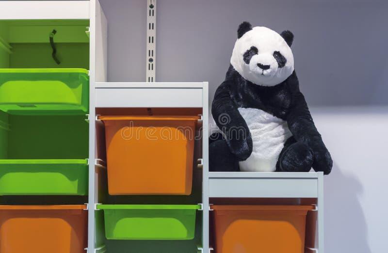 Weicher Spielzeugpanda auf dem Gestell mit farbigen Plastikkästen stockfotos