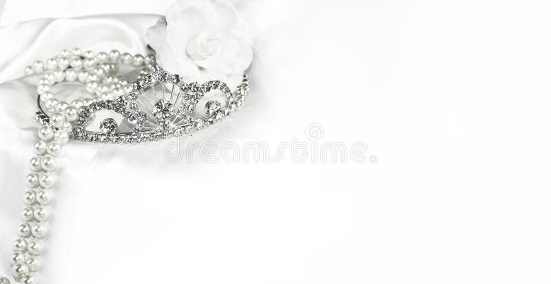 Weicher weißer Brauthintergrund der Brauthochzeitsdekorationen, silberne Krone und Perlen auf Satin mit Raum für Text stockfoto