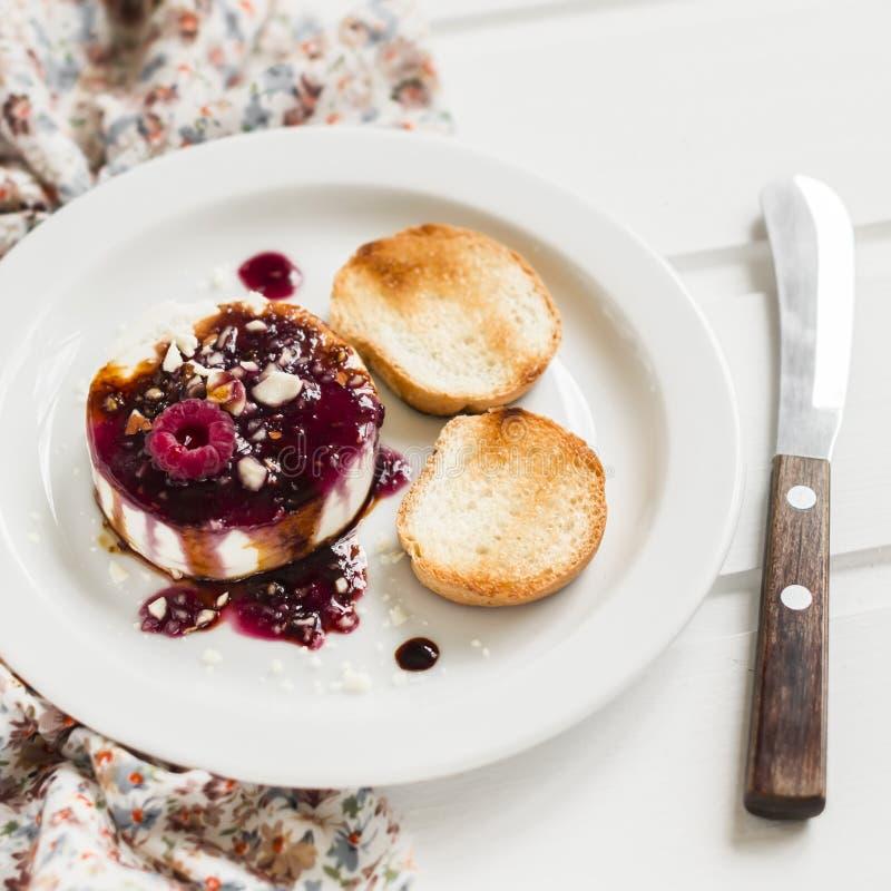 Weicher Ziegenkäse mit Beerensoße, Balsamico-Essig und Nüssen - ein köstlicher Aperitif mit Wein lizenzfreie stockfotos