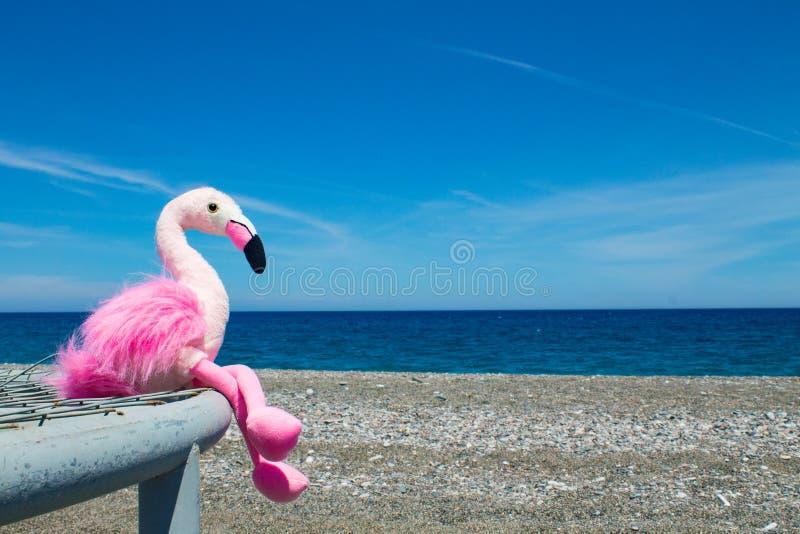 Weiches rosa Flamingospielzeug, das auf einem Metallgitter auf einem Pebble Beach durch das blaue Meer sitzt lizenzfreies stockfoto